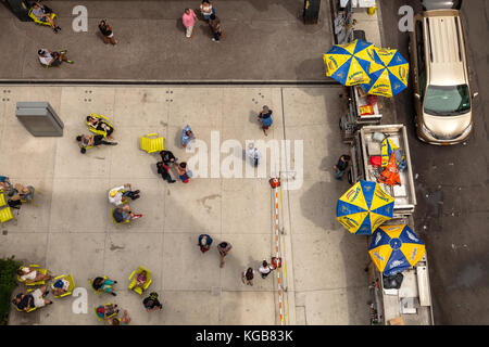 View from above as the New Yorkers are enjoying their lunchtime in front of the lunch trucks on the street of New - Stock Photo
