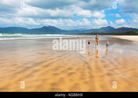 Happy family - mother, children have fun, run by water pool along sea surf on sand beach. Red island beach, pantai - Stock Photo