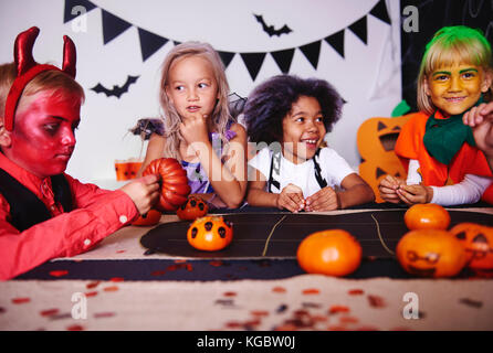 Children playing in costume at halloween party - Stock Photo