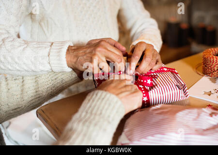 Unrecognizable senior couple in sweaters wrapping Christmas gift. - Stock Photo