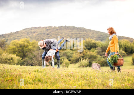 Senior couple with grandaughter in nature. - Stock Photo
