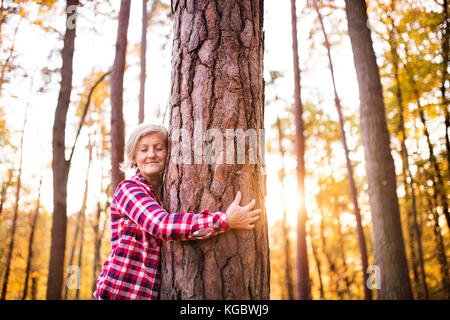 Senior woman on a walk in an autumn forest. - Stock Photo