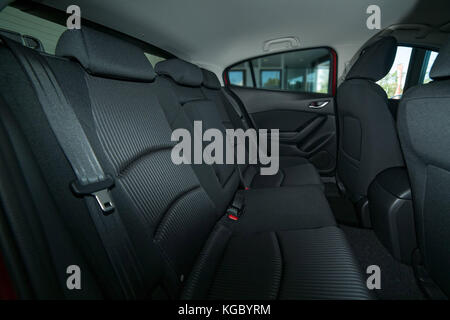Modern car interior with back seat with seat belts, front seats and roof with a grab handle - Stock Photo