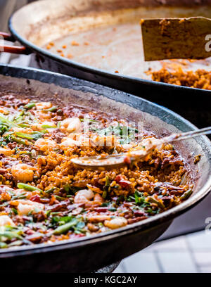 Paella dish with shrimp, closeup. Colorful Spanish paella rice in pan with vegetables and prawns. Empty pan in background - Stock Photo