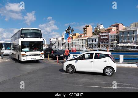 Tourbus and rental car in the town centre of Agios Nikolaos, Crete, Greece - Stock Photo