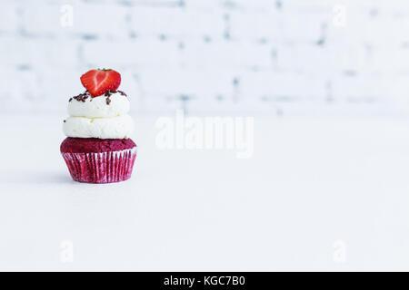 Red velvet capcake with mascarpone cream with strawberry. White background. - Stock Photo