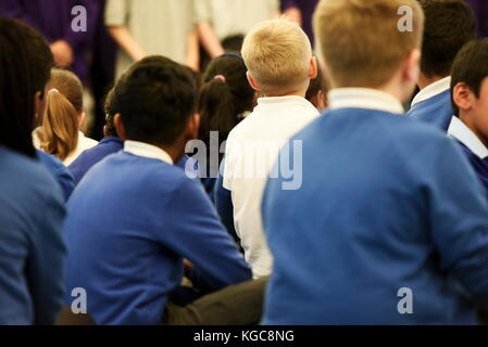 Young primary school aged children sit in a school assembly - Stock Photo