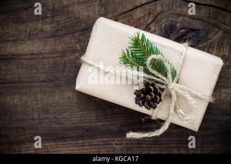 Vintage gift box wrapped in kraft paper and tied with burlap twine decorated with fir tree branches and a pine cone - Stock Photo