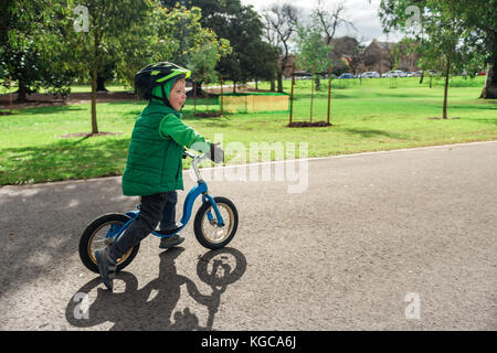 Cute smiling little boy riding balance bike in Adelaide city during cold winter day - Stock Photo