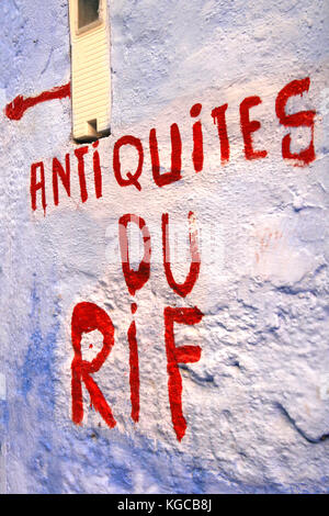 Rif antiquities, written on a blue wall of Chefchaouen. Morocco. - Stock Photo