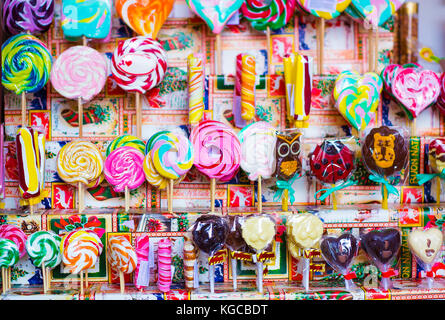 Great choice of colorful caramel on stick and chocolate candy for sale in shop window - Stock Photo