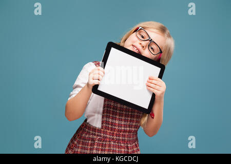 Cute little girl in red dress, white shirt and glasses holds empty tablet - Stock Photo