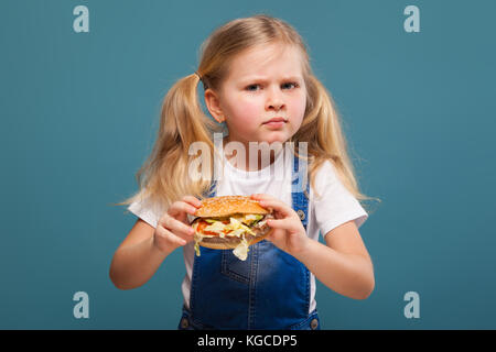 Adorable cute little girl in white shirt and jean jumpsuit with hamburger - Stock Photo