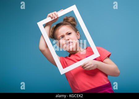 Beautiful cute little girl in pink dress holds picture frame - Stock Photo