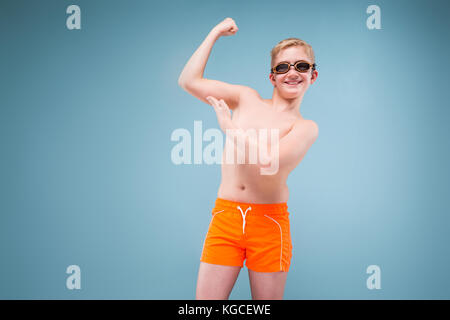 blond student in swimming trunks and goggles for swimming - Stock Photo