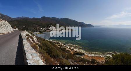 Corsica, Cap Corse: winding road of the western coast of the Cap Corse with view of one of the many black beaches - Stock Photo