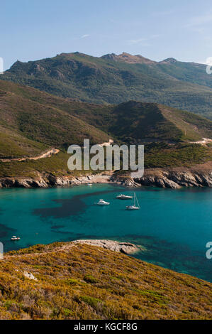 Corsica: boats in the crystal clear water of Anse d'Aliso or Plage d'Alisu, one of the most remote beaches of the - Stock Photo