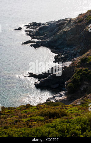 Corsica: cliffs and Mediterranean maquis at Anse d'Aliso (Plage d'Alisu), one of the most remote beaches of the - Stock Photo