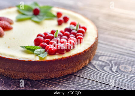 Fresh cheesecake with berries on a wooden background. - Stock Photo
