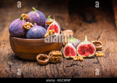 Figs and walnuts.. A few figs and walnuts in a bowl on an old wooden background. - Stock Photo