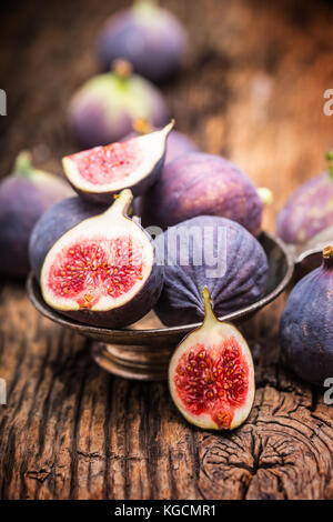 Figs. A few figs in a bowl on an old wooden background. - Stock Photo