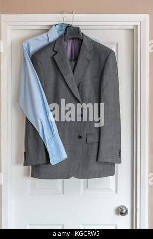 Mens formal business suit hanging over doorway, with blue shirt. - Stock Photo