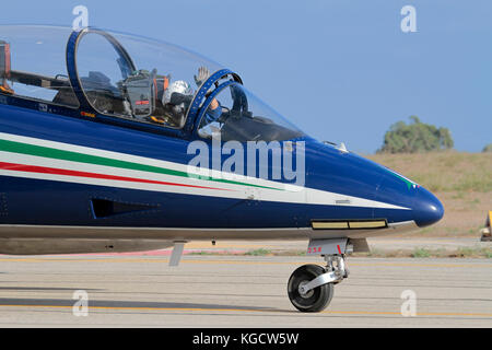 A pilot of the Italian Air Force Frecce Tricolori aerobatic display team waves to the crowd at an airshow - Stock Photo