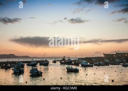 Sunrise over the harbour at Lyme Regis in Dorset, UK. - Stock Photo