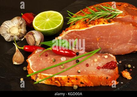 Raw pork chops with spices. Sliced meat prepared on the grill - Stock Photo