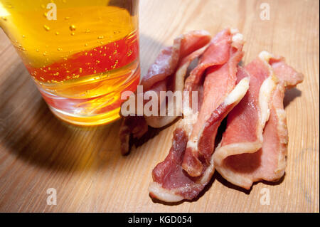 Board with home beef jerky - dried spicy meat, a large glass of beer. - Stock Photo