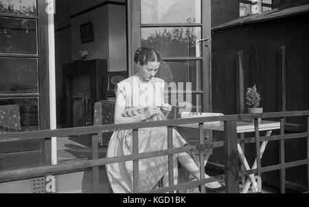 1940s, Britain, young lady a dress sitting alone on a home veranda knitting. Hand-knitting was a popular pastime - Stock Photo