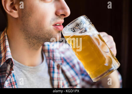 Handsome young male brewer in apron tasting fresh beer while standing in front of metal containers - Stock Photo