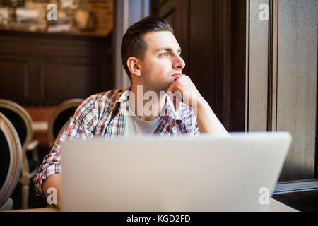 Young successful businessman working on a laptop while sitting in cafe during work break lunch - Stock Photo
