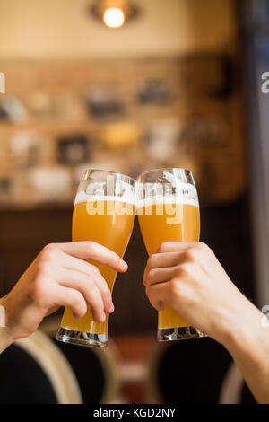 Men cheers with beer in glasses in pub. - Stock Photo