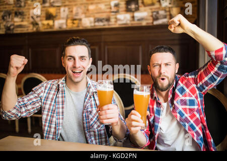 Cheerful male friends having fun at the beer pub celebrating victory of their favorite team watching game on TV - Stock Photo