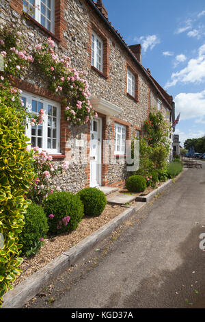 Rose covered brick and flint cottages in the picturesque village of Burnham Market in Norfolk. - Stock Photo