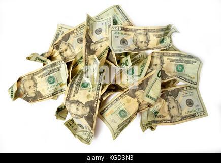 Horizontal shot of a pile of crumbled twenty dollar bills on a white background. - Stock Photo