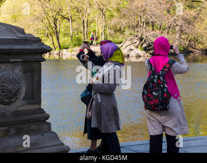 Three ladies wearing headscarves take pictures of a pond. - Stock Photo