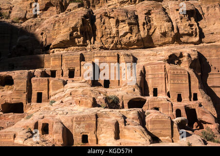 Pink sandstone carved Nabataean tombs, Street of Facades, lit by early morning sun, Petra, Jordan, Middle East - Stock Photo