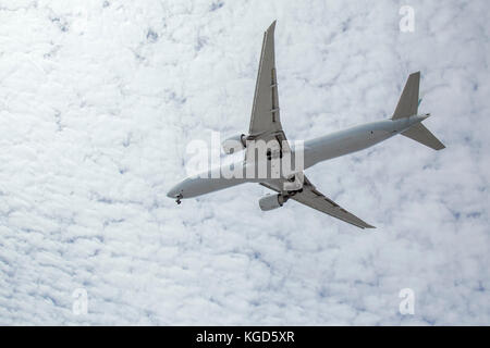 Commercial airliner flying overhead preparing for landing at LAX with brilliant clouds in the background - Stock Photo