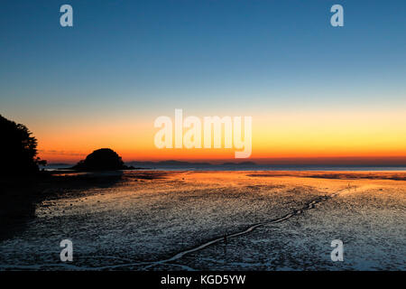 after a sunset over mud field revealed by low tide on an island in south Korea - Stock Photo
