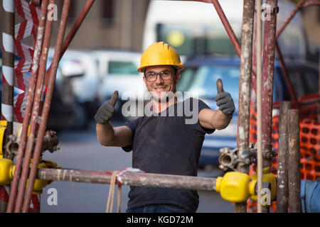 Young italian building worker, engineer smiling and showing thumb up. Streets of Sicily, reportage, Palermo, Italy. - Stock Photo