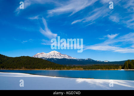 Mount Shasta in winter with lake on foreground - Stock Photo