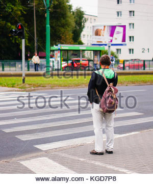 POZNAN, POLAND - SEPTEMBER 12, 2013: Man waiting in front of a zebra crossing with red light - Stock Photo
