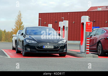 TOIJALA, FINLAND - OCTOBER 17, 2015: Three Tesla Model S cars are being charged at Tesla Supercharger station. Currently - Stock Photo
