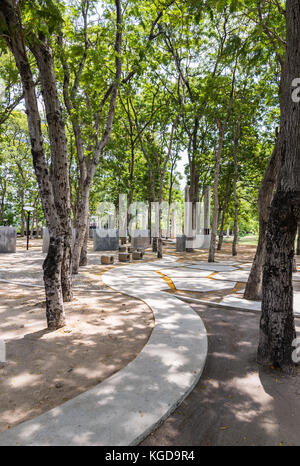 Concrete walkway to the seat area under the shade from the tree in the urban park. - Stock Photo