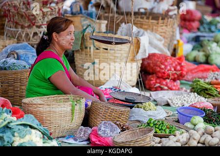 Burmese woman wearing thanaka on her face selling vegetables at food market in village along Inle Lake, Nyaungshwe, - Stock Photo