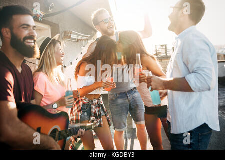 Group of happy friends having party on rooftop - Stock Photo