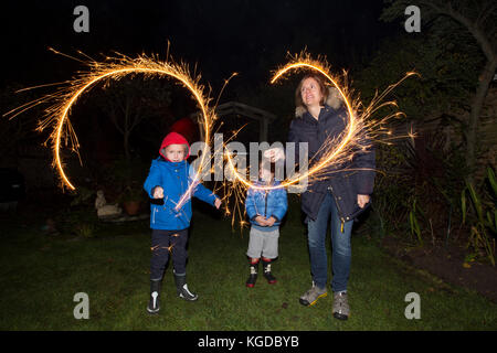 Family with hand held sparkler fireworks in a residential garden on Bonfire Night marking the anniversary of the - Stock Photo