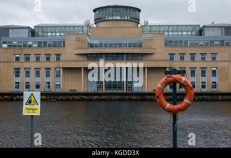 Victoria Quay, Scottish Government office building, Leith, Edinburgh, UK, with lifebelt and triangle danger deep - Stock Photo